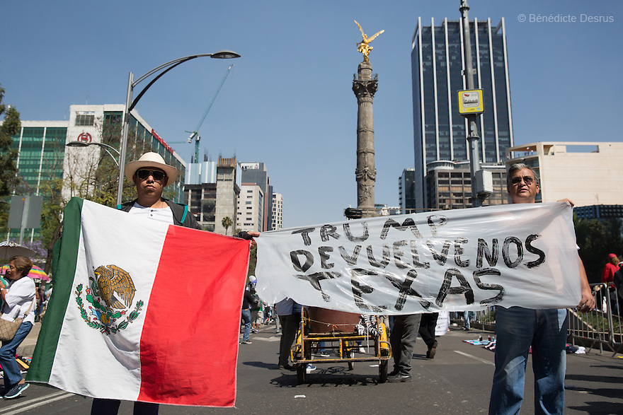 "Two Mexican men hold a sign with message: ""Trump gives Texas back to Mexico"" during an anti-Trump march in Mexico City, Mexico on February 12, 2017. Photo by Bénédicte Desrus"