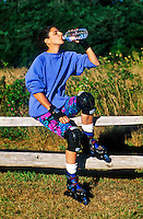 Woman drinking water after rollerblading.