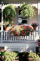 Curb appeal container garden on house front porch with impatiens, hanging plants, pots, sun and shade in summer