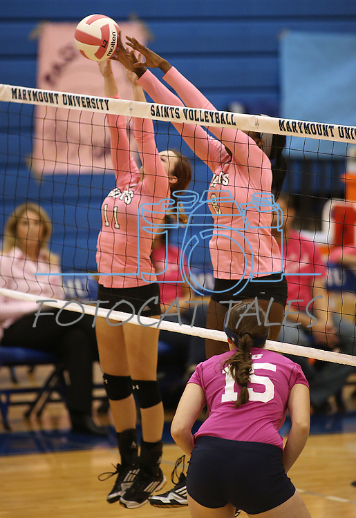 Marymount's Bri Fitzpatrick, left, and Morgan McAlpin get a block during a college volleyball match against Shenandoah at Marymount University in Arlington, Vir., on Tuesday, Oct. 8, 2013.<br /> Photo by Cathleen Allison