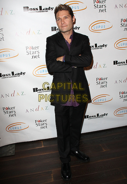 "COREY FELDMAN. Lupus LA Raises Awareness with ""Get Lucky for Lupus"" held At Andaz Hotel, West Hollywood, California, USA..February 25th, 2010.full length black trousers suit jacket purple shirt arms crossed  .CAP/ADM/KB.©Kevan Brooks/AdMedia/Capital Pictures."