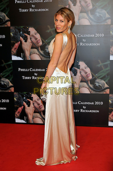 HOFIT GOLAN .Attends the Pirelli Calendar 2010 Gala Dinner, Old Billingsgate, Old Billingsgate Walk, London, England, UK,.20th November 2009..full length white silk satin dress backless low looking over shoulder back rear behind .CAP/PL.©Phil Loftus/Capital Pictures.