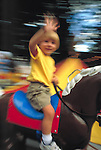 smiling young boy waving from carousel horse