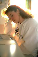 College bound 17 yr. old girl reading a book in family kitchen.  Lake Minnetonka Minnesota USA