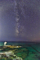 A boat under the Milky Way in Andros, Greece