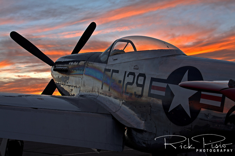 A North American P-51D Mustang sits on the ramp at sunset.