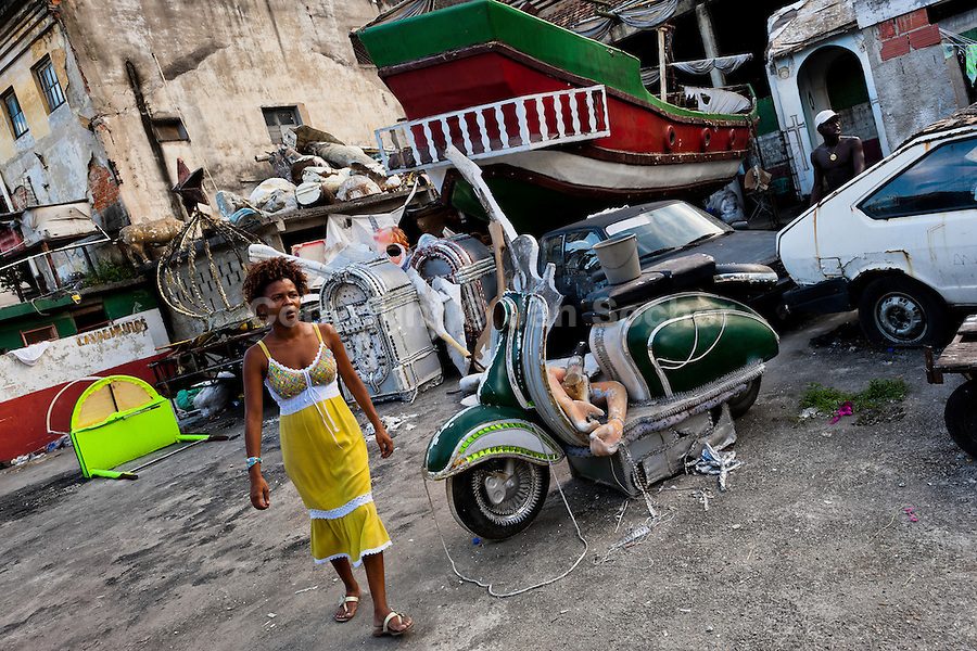A Brazilian woman walks among the discarded carnival statues on the work yard behind the Samba school workshops in Rio de Janeiro, Brazil, 15 February 2012. Most of the large carnival floats, colorful designs and fancy costumes are dismantled, cut into pieces or simply thrown into garbage right after the last day of the Carnival. The low-tech materials as fiberglass, plastic or polystyrene, which most of the of the carnival floats and statues are made of, are stocked in the warehouses to be recycled and used in the future parades. However, there is no use for some of the statues so they slowly fall apart into pieces forming a ?Carnival cemetery? in the industrial yards around the port of Rio de Janeiro.
