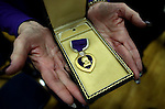 Peggy Eddington-Smith holds her father's purple heart medal following a ceremony, in Dayton, Nev., on Saturday, Sept. 20, 2013. After 14 years of searching for relatives of World War II Private John F. Eddington, the medal and other personal items, found in Missouri, were returned to Eddington-Smith. <br /> Photo by Cathleen Allison/Las Vegas Review-Journal