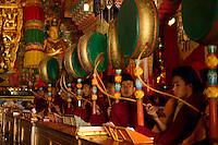 Buddhist Monks playing drums in a Losar ceremony inisde a monastery, Sikkim, India