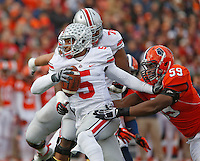 Ohio State Buckeyes quarterback Braxton Miller (5) tries to scramble out of trouble from Illinois Fighting Illini defensive lineman Tim Kynard (59) in second quarter at Memorial Stadium in Champaign, Illinois on November 16, 2013.  (Chris Russell/Dispatch Photo)