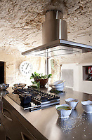 A contemporary stainless steel work unit dominates this intimate country kitchen with a low stone ceiling