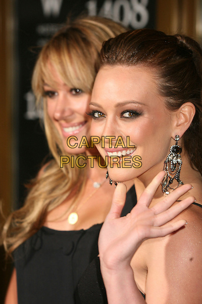 "HAYLIE DUFF & HILARY DUFF.""1408"" World Premiere at Mann's National Theatre, Westwood, California, USA..June 12th, 2007.headshot portrait sisters siblings family earrings dangling hand palm waving smokey eyes.CAP/ADM/BP.©Byron Purvis/AdMedia/Capital Pictures"