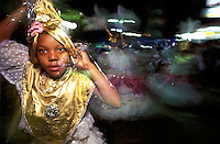 Tugging on a gleaming turban, a young sambista, or samba dancer, parades through the streets of the southern Brazilian town of Camboriú on the eve of Ash Wednesday.