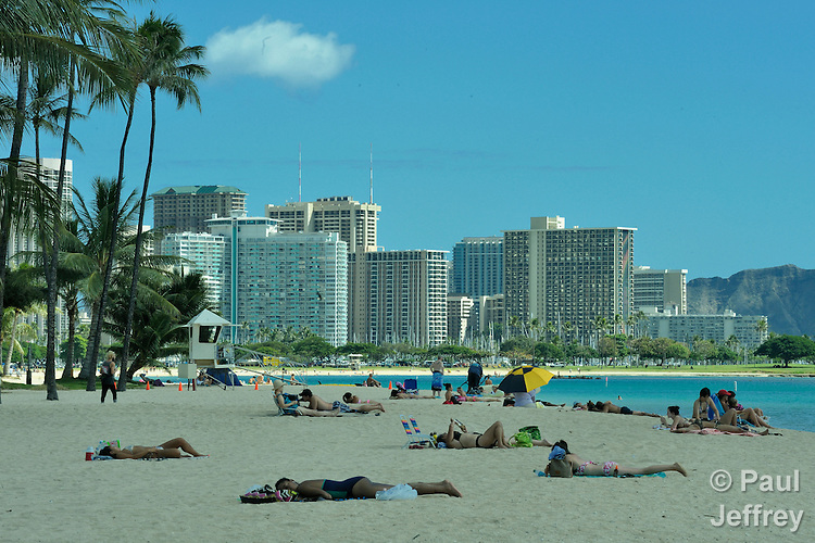 A beach in Honolulu, Hawaii, with the hotels of the Waikiki neighborhood in the background.