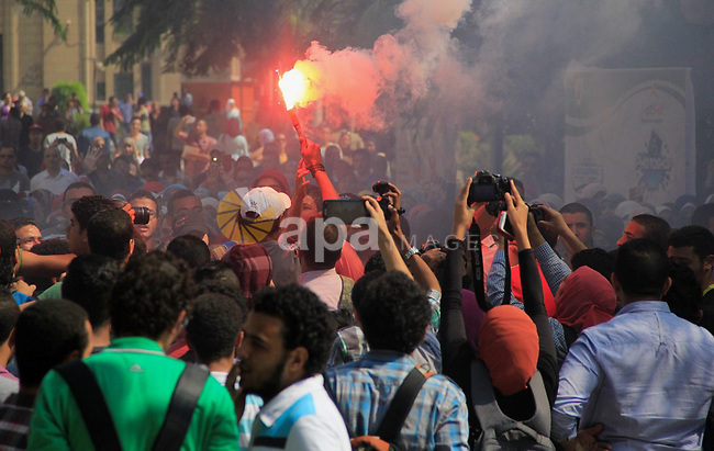Egyptian students who support Muslim Brotherhood in the Cairo University hold fireworks during a protest against the military rule, outside Cairo University on October 15, 2014. Supporters of ousted Egyptian President Mohamed Mursi, continue to hold small, scattered protests despite a crackdown after his ouster in July 2013. Photo by Amr Sayed
