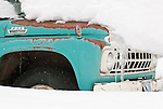 An old truck sits under a blanket of snow in Wilson, Wyoming.