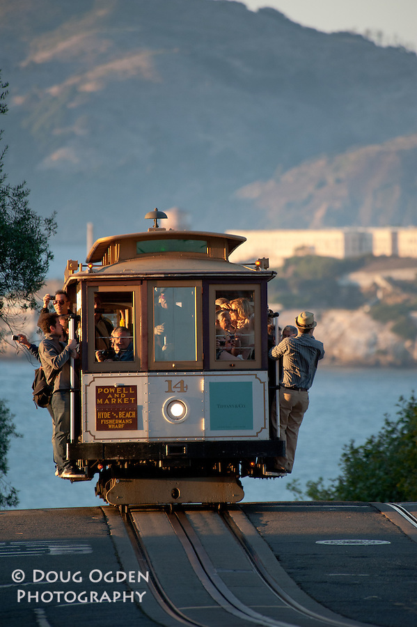 Tourists riding the Powell and Hyde cable car in San Francisco, Alcatraz in the back ground