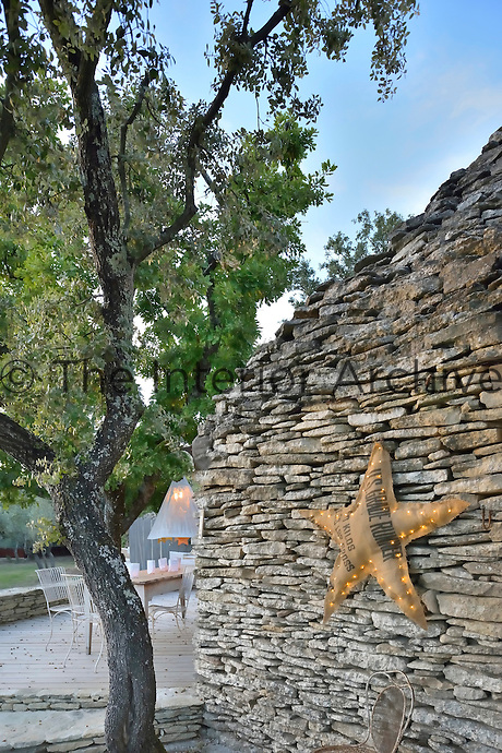 A dry stone wall on the terrace is decorated with an illuminated star