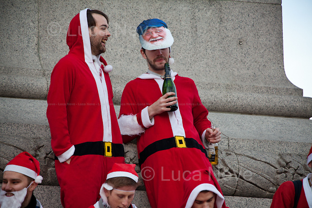 """London, 15/12/2012. Hundreds of people dressed as Santa Claus and similar other outfits gathered in Trafalgar square to celebrate the annual event called """"Santacon"""". After a funny battle fought using Brussels sprouts, around 6 PM, one of the Santas climbed the 20 meters Christmas tree. When he came down he was held for a while by the Heritage Wardens but at the end he managed to escape throughout the crowd."""