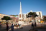 People enjoying a sunny spring afternoon in Plaza de la Merced, Malaga, Spain