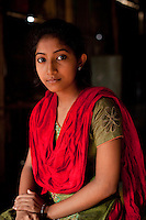 "Tamanna Jinnat (13) sits for a portrait in the meeting hut of a Children's Group in Bhashantek Basti (Slum) in Zon H, Dhaka, Bangladesh on 23rd September 2011. Tamanna explains, ""we have an organised system: we have a list of girls who are potential child brides and we check on them. Another initiative is making sure that there is birth registration for babies so that there will be a proof of their age."" Tamanna's mother said that ""at your age, you are not aware of the benefits of an early marriage,"" to which Tamanna replied, ""how about issues of maternal mortality from being too young to bear children?"". She also wants to be allowed to work part time so she can support her own education and independence. The Bhashantek Basti Childrens Group is run by children for children with the facilitation of PLAN Bangladesh and other partner NGOs. Slum children from ages 8 to 17 run the group within their own communities to protect vulnerable children from child related issues such as child marriage. Photo by Suzanne Lee for The Guardian"