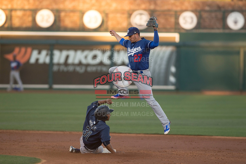 Los Angeles Dodgers shortstop Omar Estevez (27) leaps over DeAires Moses (31) as he attempts to catch a ball during a Minor League Spring Training game against the Seattle Mariners at Camelback Ranch on March 28, 2018 in Glendale, Arizona. (Zachary Lucy/Four Seam Images)
