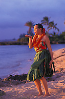 Young woman with lei and ti leaf skirt blowing a kiss during an auana hula dance on the beach