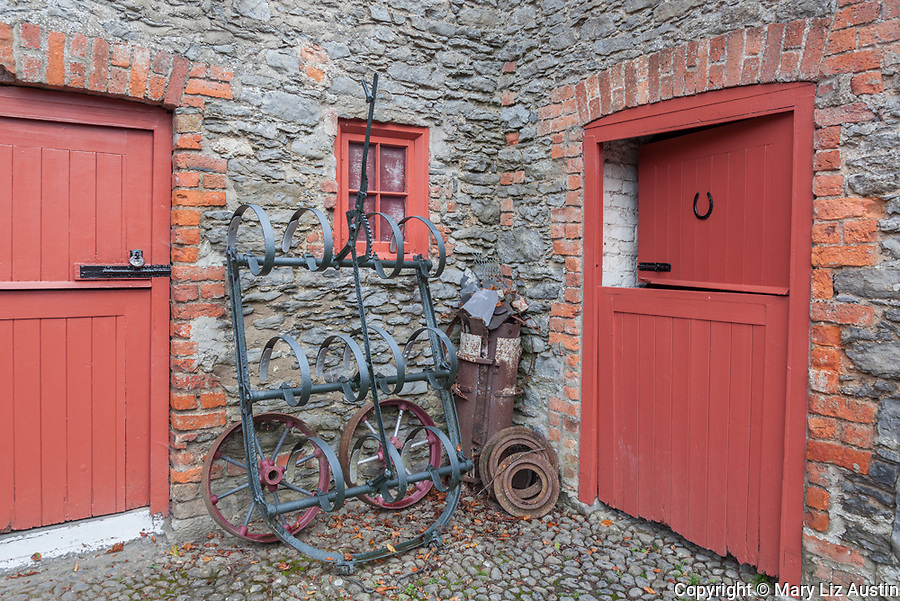County Clare, Ireland Stone walls and cobbled stable yard with colorfully painted wagon wheels and stable doors at Bunratty House,  Bunratty Folk Park