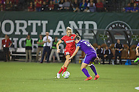 Portland, Oregon - Sunday April 17, 2016: Portland Thorns FC midfielder Allie Long (10) is defended by Orlando Pride defender Laura Alleway (5). The Portland Thorns play the Orlando Pride during a regular season NWSL match at Providence Park. The Thorns won 2-1.