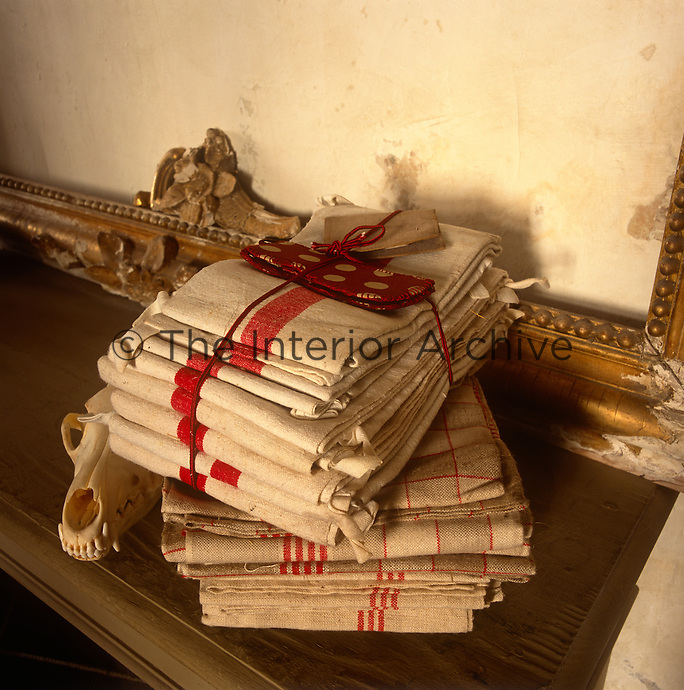 A pile of red and white linens are tied with red string on the edge of a cabinet. Standing behind is an empty gilded picture frame.