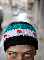 A young boy wears a hat bearing the rebel colours - the Syrian flag before the Baathist takeover in 1963. He didn't want his full face shown. Zabadani is the only town in Syria officially held by the rebels. The hill town which is surrounded by government forces.Protests against the ruling Baathist regime of Bashar al-Assad erupted in March 2011. Although they were initially peaceful,  they were violently repressed by the Syrian army and police. In response to being ordered to shoot unarmed civilians, large numbers of men deserted the army and formed the Free Syrian Army. The protest movement has now turned into an armed uprising with clashes between the regular army and the Free Syrian Army taking place in early 2012..