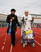 Rollatorloop in het Olympisch Stadion in Amsterdam. Wandelevenement  voor ouderen met een rollator. Een non legt lachend het parcours af