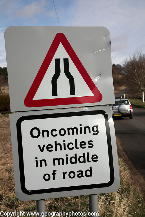 Road narrows oncoming vehicles in middle of road sign
