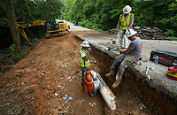 NWA Democrat-Gazette/BEN GOFF @NWABENGOFF<br /> Jerry Heath (from left), Jaime Almaraz and Bryan Lowery with Crossland Heavy Contractors move a water line Wednesday, July 10, 2019, as part of a tunnel construction project on Highlands Boulevard in Bella Vista. The tunnel is one of the eleven namesake tunnels planned for the 11 Under trail system under construction on the West side of Bella Vista.