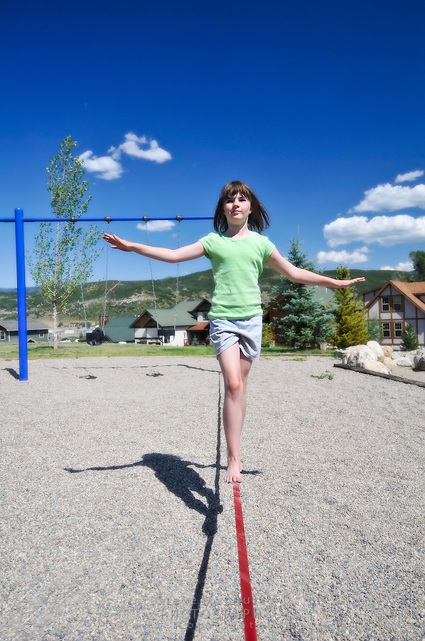 Young girl balancing on slackline on neighborhood playground, Steamboat Springs, Colorado