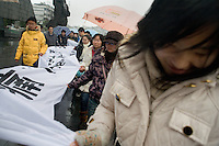Young people carry a banner in memory of the victims of the Nanjing Massacre outside the Memorial Hall of the Nanjing Massacre in Nanjing, Jiangsu, China on Dec. 13, 2009. On Dec. 13, 2009, thousands of people visited The Memorial Hall of the Nanjing Massacre in Nanjing, Jiangsu, China, to remember those who died at the hands of Japanese soldiers in 1937-8.  The day marked the 72nd anniversary of the start of the massacre. The historical account has always been mired in controversy, and differing opinions on what actually happened have been a consistent obstacle to relations between China and Japan.  China's official account of history states that 300,000 people were killed by Japanese forces over a 6-week period starting Dec. 13, 1937