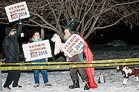 Bonnie (with green) and Dan Swanson of Manchester, New Hampshire, join satirical presidential candidate Vermin Supreme as he protests his exclusion from the Lesser-Known Candidates Debate outside Saint Anselm College's New Hampshire Institute of Politics in Goffstown, New Hampshire. Supreme participated in previous debates, but was told he would be not allowed back this year because of an incident during the 2011 debate in which Supreme threw glitter on candidate Randall Terry. The college put up police tape behind which the candidate was told to stand without risking arrest. Supreme's platform advocates a pony-based economy, using zombies to solve the energy crisis, and other outlandish ideas. Supreme has been on the New Hampshire primary ballot in 2008 and 2012, though he has began running for president in 1992.