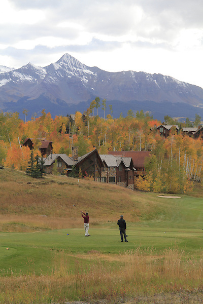 Male golfers teeing-off with Wilson Peak (14,017 ft) behind, Telluride, Colorado.