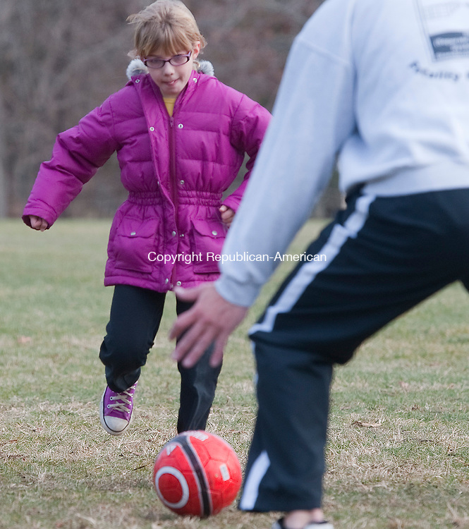 WATERBURY, CT-122713JS05-Avery Johnston, 8, of Greenville SC, tries to slip a shot past her uncle Jim Colby of Woodbury as they play a pick-up soccer game with other family members Friday at Hollow Park in Woodbury.<br /> Jim Shannon Republican-American