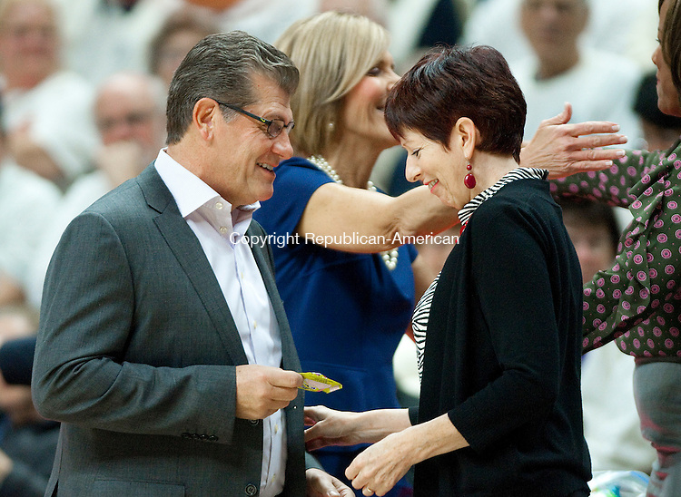 STORRS, CT--- -12015JS01--UConn head coach Geno Auriemma hands a gift to Notre Dame head coach Muffet McGraw prior to their game Saturday at Gampel Pavilion in Storrs. <br /> Jim Shannon Republican-American