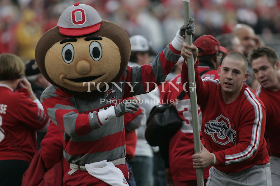 18 Nov 2006: Brutus the Buckeye mascot and an OSU cheerleader runs the Ohio State flag ahead of the team as the they take to the field before the start of Ohio State's 42-39 win over Michigan in a college football game at Ohio Stadium in Columbus, OH.