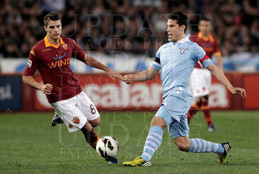 Calcio, Serie A: Roma vs Lazio. Roma, Stadio Olimpico, 8 aprile 2013..Lazio midfielder Hernanes, of Brazil, is challenged by AS Roma forward Erik Lamela, of Argentina, left, during the Italian serie A football match between A.S. Roma  and Lazio at Rome's Olympic stadium, 8 april 2013..UPDATE IMAGES PRESS/Isabella Bonotto