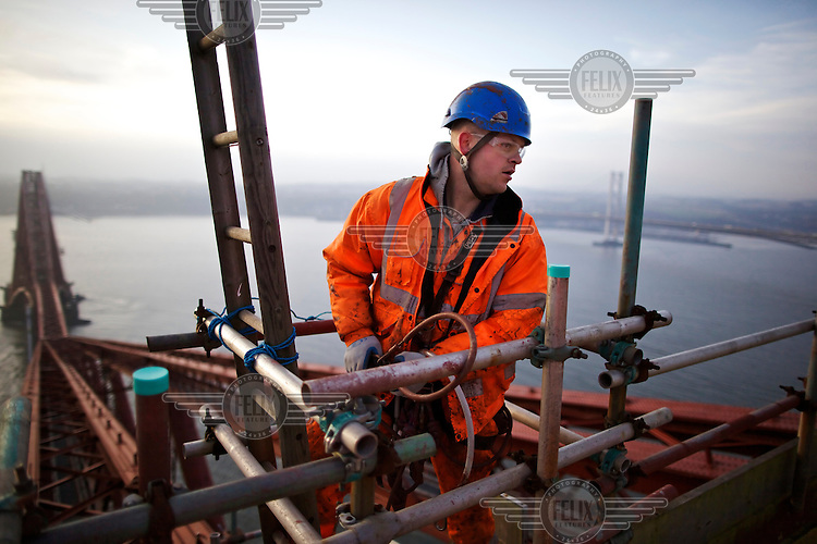 Abseiler preparing to carry out touch points from the top of the Fife cantilever on the 125 year old Forth Rail Bridge which spans the river Forth near Edinburgh. Network Rail, the operator of the rail track that leads over the bridge, has spent 10 years and GBP 130 million repainting the 230,000 square metres of steel and 6.5 million rivets on the bridge. The iconic red paint used on the bridge is made to match the red-oxide paint used over 100 years ago. The bridge will now need no further painting for at least 20 years.