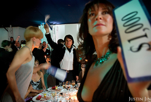 "Rustam Tariko, billionaire oligarch owner of the vodka brand ""Russian Standard"", waves mock dollar bills to pledge donation during a charity ball in Moscow."