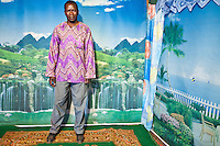 "Lens Photo Studio, Kibera, Nairobi, Kenya. Peter Otieno                      shoots passport pictures and portraits from his Kibera studio, often using an old Pentax K1000 camera.               According to Olendo ""When making a picture you have to include the feet. If people can't see their feet they might not pay you. They might say 'I came in here with feet and you've forgotten them. This picture is no good.' """