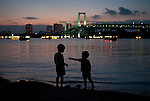 Tokyo, Odaiba bay, August 2009. Two boys playing on the beach at dusk in front of the Rainbow bridge.
