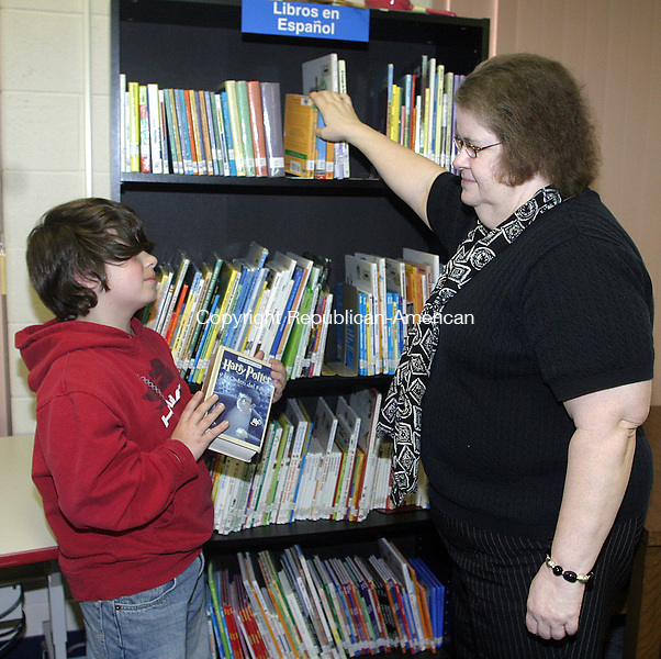 TORRINGTON, CT -16 MAY 2008 -051608DA03-Marilyn Hoitt, right, media specialist for Forbes School in Torrington looks over the bilingual/spanish book collection with 5th graders, Ryan Jacquemin, left, in the schools library on Friday. As the city's population is changing with more Spanis-speaking immigrants and test scores reflect nationwide that girls are far outpacing boys in reading, the role of schools libraries has changed. An emphasis is now on making sure libraries are stocked with books that will attract boys, and books that will help increase interest in reading for all students.<br /> Darlene Douty/Republican-American