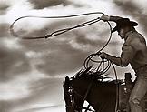USA, California, Oxnard, Southern California, a cowboy swings his rope while running on horseback (B&W)