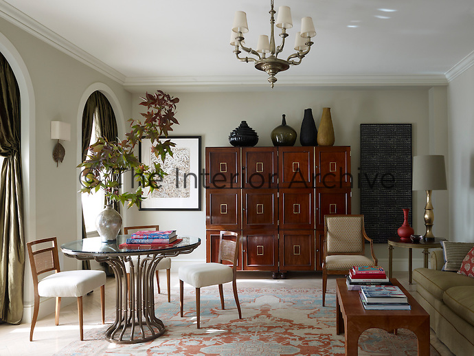 Artworks by Joe Brainard and Lynn Davis flank a pair of English museum cabinets in the sitting room
