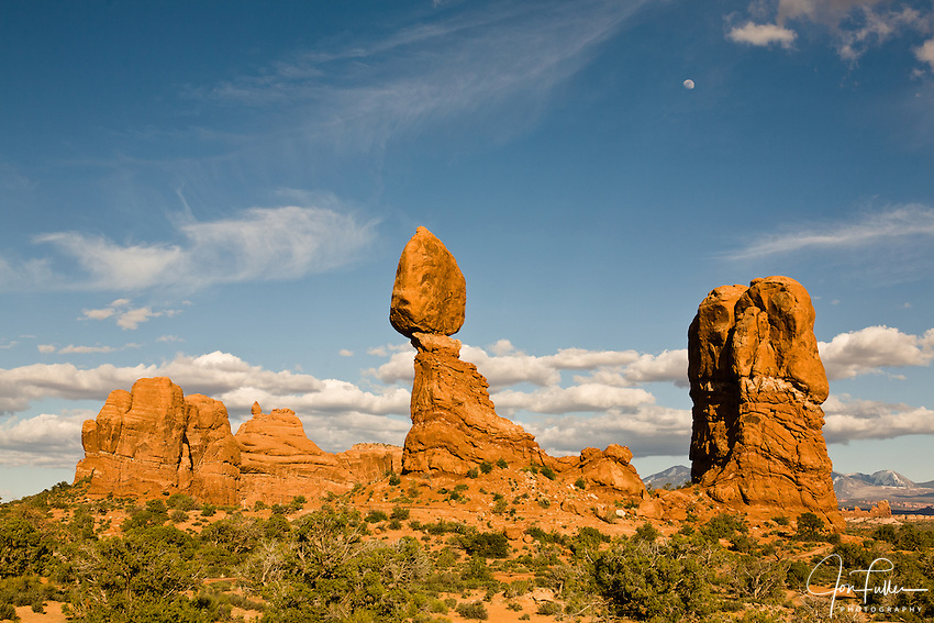 The moon over Balanced Rock in Arches National Park, Moab, Utah, USA with cirrus and cumulus clouds.